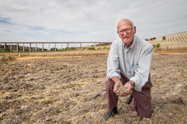 José María coge un puñado de tierra seca en una finca junto al puente de Hacho./JORGE PASTOR