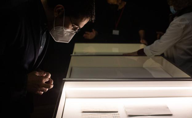 Observando el manuscrito en la vitrina donde se podrá ver en la exposición.