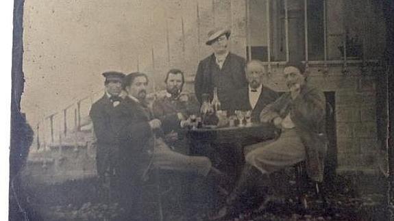 El holandés es el tercero desde la izquierda, con barba, y está fumando de una pipa. Gauguin está sentado en el extremo derecho./